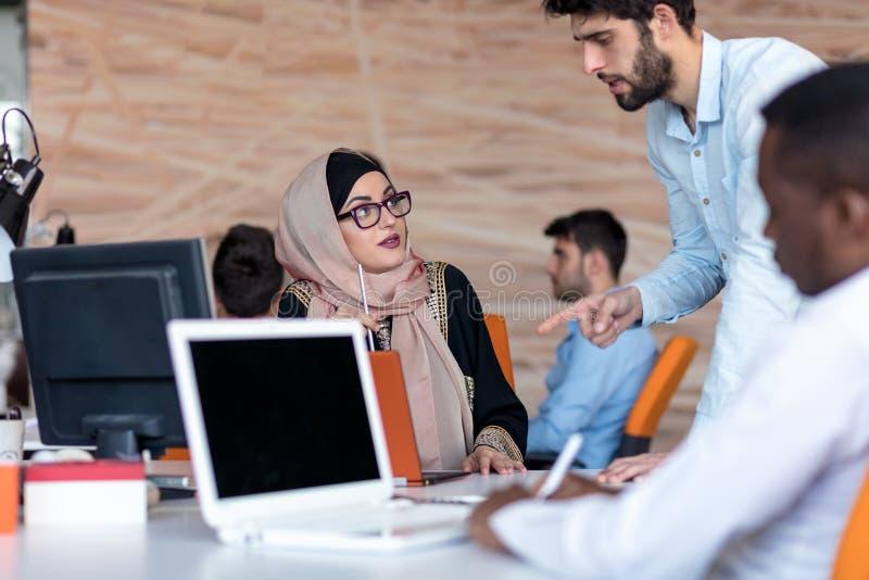 Diversi studenti di college che per mezzo del computer portatile e parlando, imparando scambiando le idee fotografia stock libera da diritti