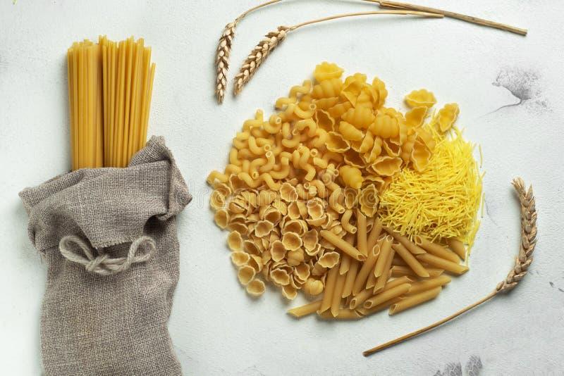 Diversi tipi di pasta e spaghetti in burlap Amidi secchi di frumento immagine stock