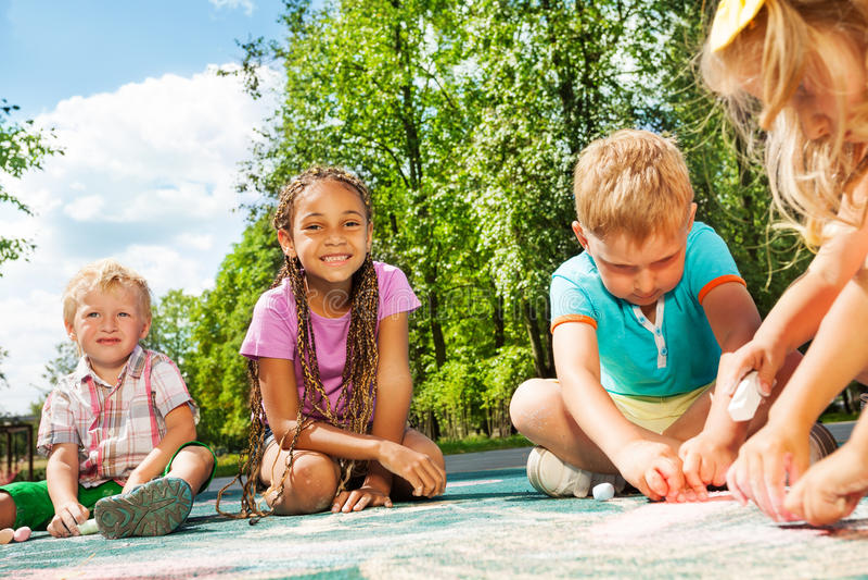 Diversidad que mira drenaje de los niños con tiza imagen de archivo libre de regalías
