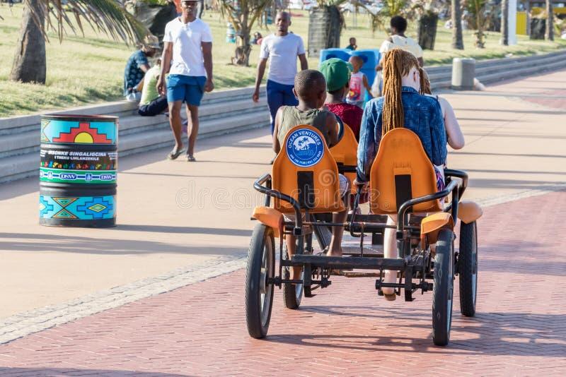 Diversidade: Dois meninos pretos e duas meninas branco-caucasianos que compartilham de um quadricycle para um passeio na praia de imagens de stock