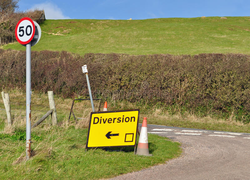 Diversion sign in countryside. A diversion sign in the countryside on a small junction with 50 mph warning sign stock image