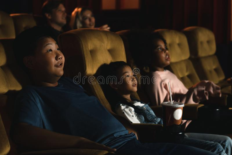 Diversité des enfants et des gens, américains noirs, caucasiens et asiatiques, s'amuser à regarder des films dans le cinéma image stock