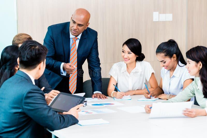 Diversiteitsteam in bedrijfsontwikkelingsvergadering met grafieken royalty-vrije stock foto