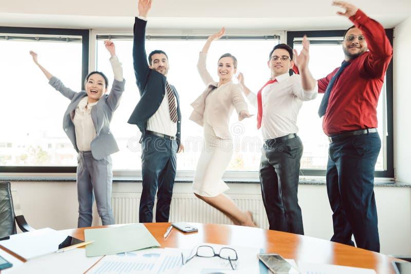 Diversiteitsteam van bedrijfsmensen die hoog in het bureau springen stock afbeeldingen