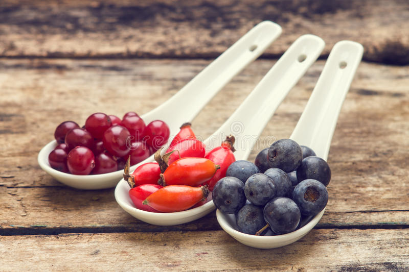 Diversity of berries on wood table. Vintage healthy food background stock image