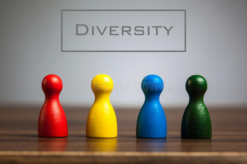 Diversity concept with four pawn figurines on table. Grey background stock image