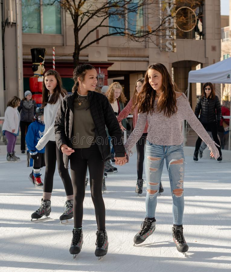 Diversity on the Ice Skating Rink. Reston VA -- November 17, 2018. A young woman and girl are ice skating together on the Reston Town Center rink; the young royalty free stock images
