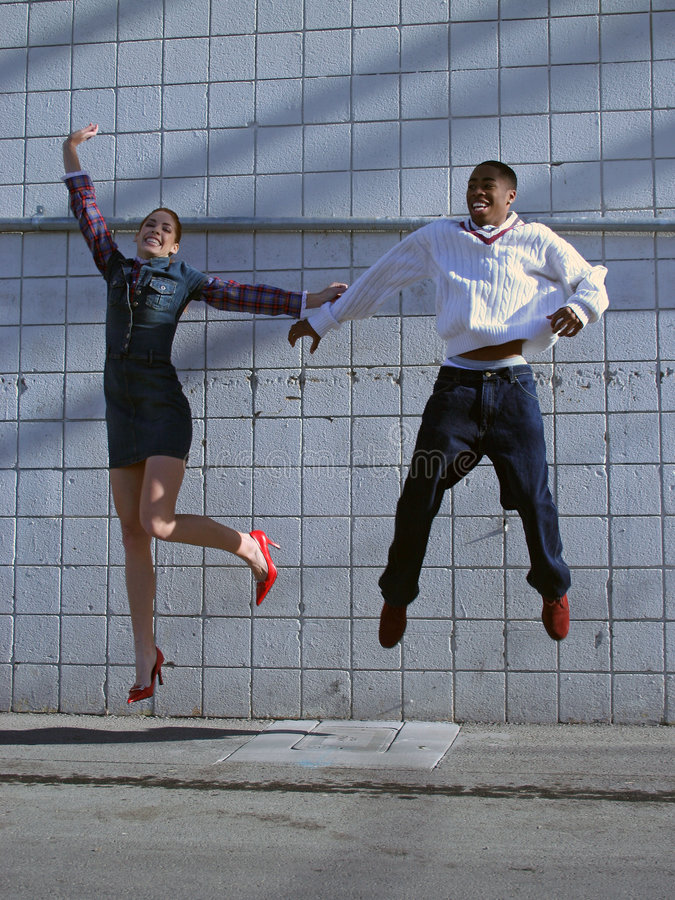 Diversity Jump. A Young interracial couple jumping for joy