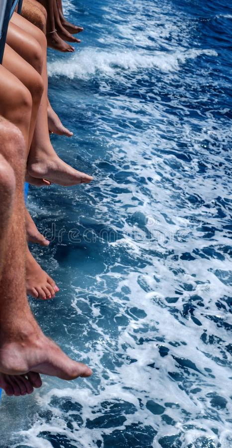 A diversity of man and women feet above the sea blue water. Close view royalty free stock image