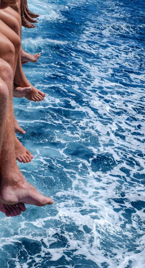A diversity of man and women feet above the sea blue water. Close view stock photography