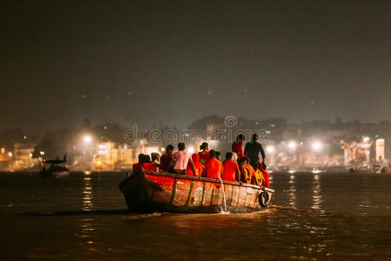 Diversity of people in the boat floating on the river are going to pray at Varanasi Ganga Aarti at holy Dasaswamedh Ghat. Diversity of people in the boat stock photography
