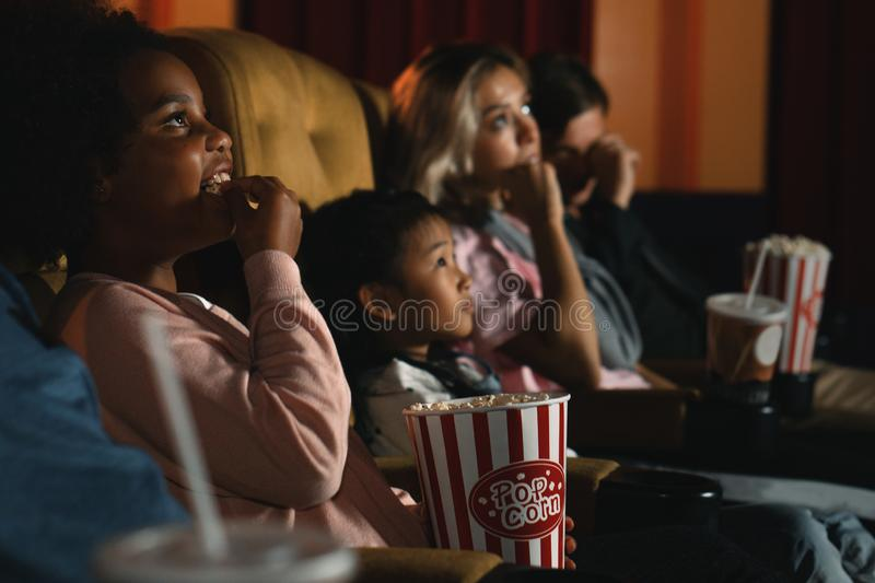 Diversity people children and young people having fun watching movie and eating popcorn in cinema theater royalty free stock photo