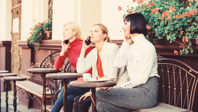 Diversity People Connection Digital Devices Browsing. Social Networking at Cafe. three girls in cafe speaking on phone stock photo