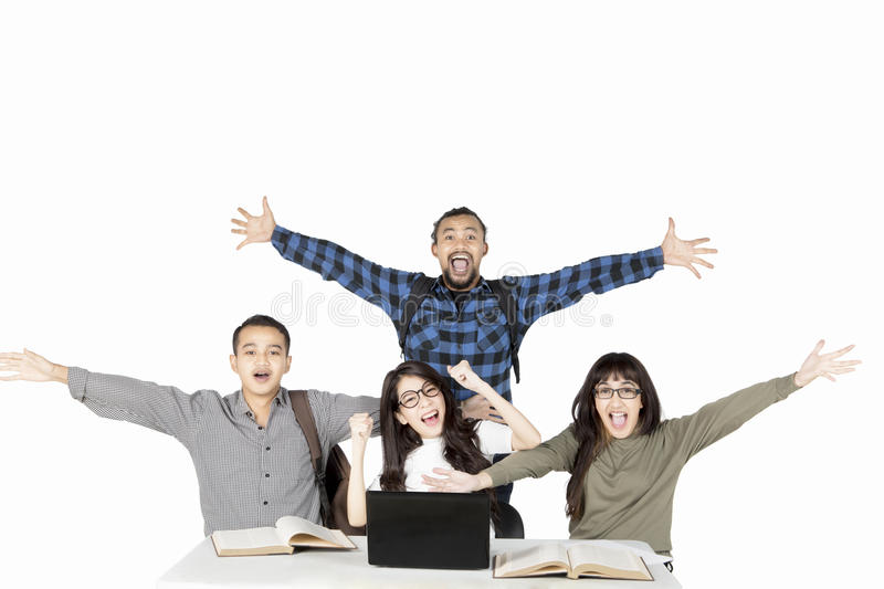 Diversity students showing happy expression. By lifting hands while studying with a laptop and books on the table royalty free stock photography
