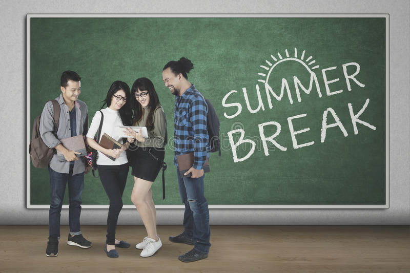 Diversity students with text of summer break. Diversity students using a digital tablet together while standing with text of summer break at the blackboard royalty free stock photo