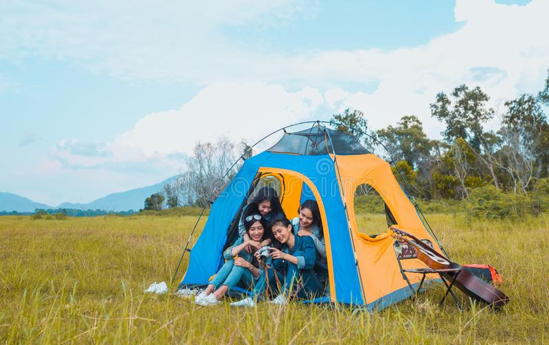 Diversity Young Asian women camping and resting. At forest looking a photo in camera happy on weekend royalty free stock photo