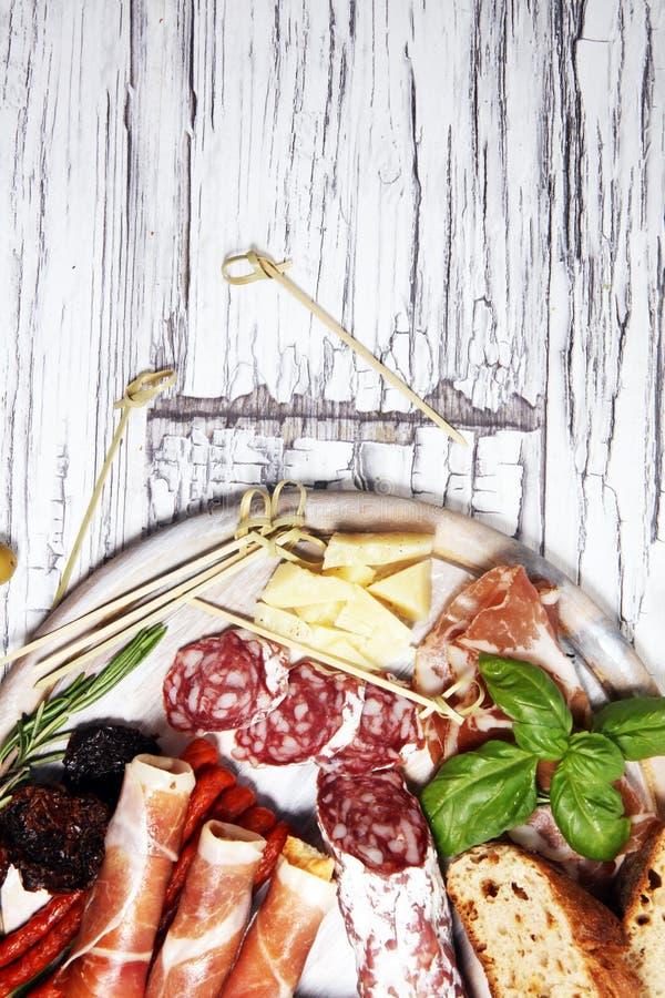 Diverso aperitivo del Antipasto Tabla de cortar con el prosciutto, el salami, el queso, el pan y las aceitunas en el fondo de mad fotos de archivo
