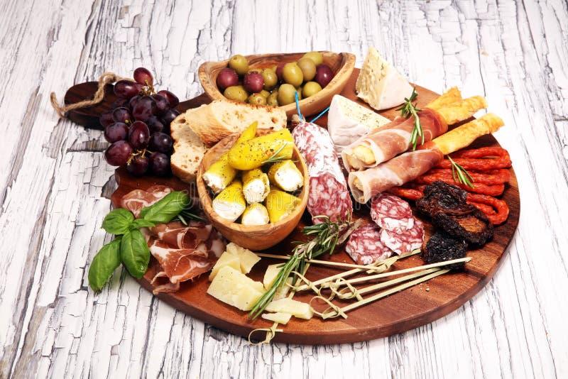 Diverso aperitivo del Antipasto Tabla de cortar con el prosciutto, el salami, el queso, el pan y las aceitunas en el fondo de mad imagen de archivo
