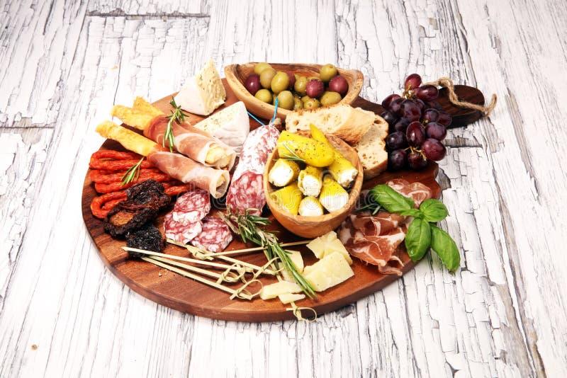 Diverso aperitivo del Antipasto Tabla de cortar con el prosciutto, el salami, el queso, el pan y las aceitunas en el fondo de mad imagenes de archivo