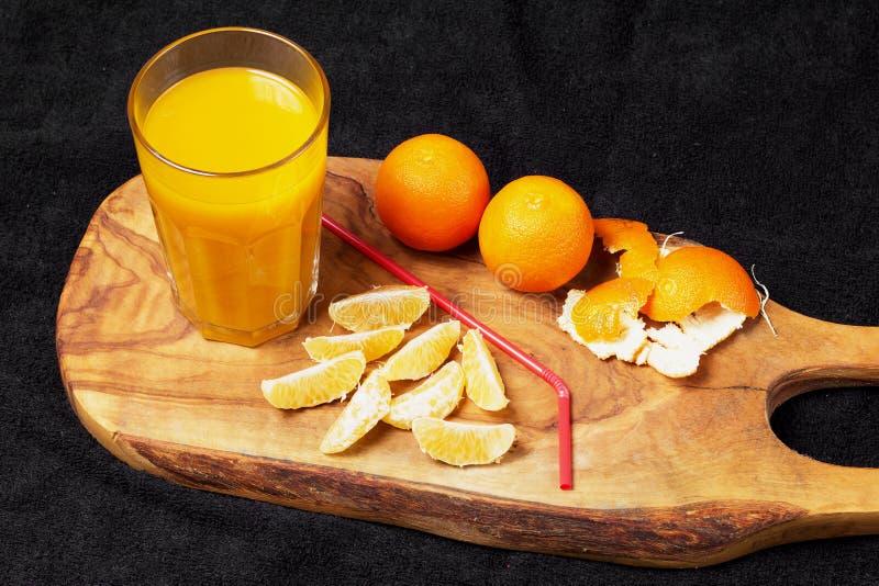 Diverso citrino maduro e um vidro do suco em uma tabela de madeira em um quadro-negro - os mandarino fotografia de stock royalty free