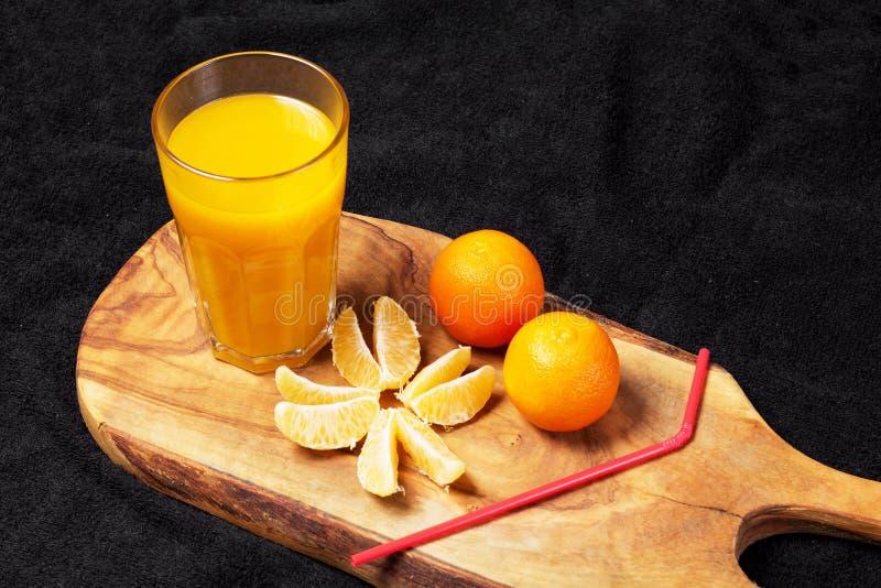 Diverso citrino maduro e um vidro do suco em uma tabela de madeira em um quadro-negro - os mandarino imagens de stock royalty free