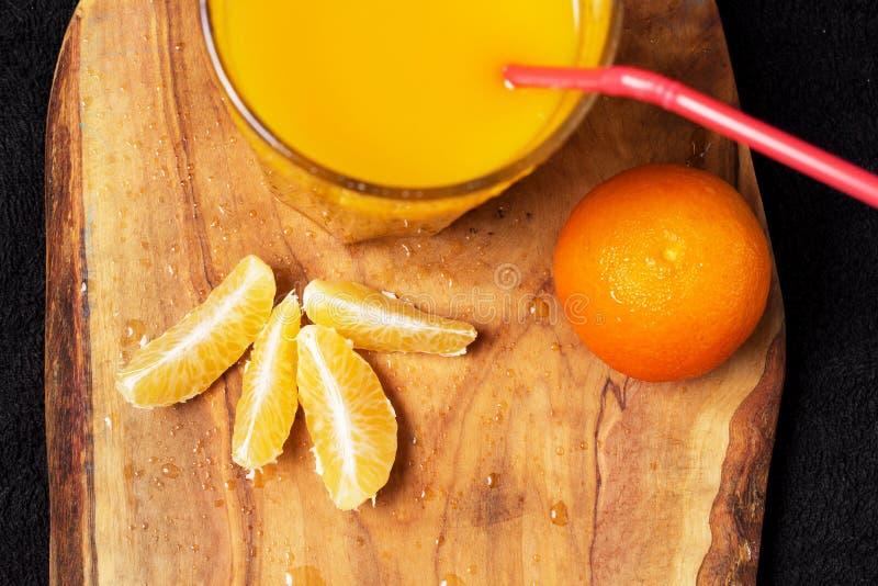 Diverso citrino maduro e um vidro do suco em uma tabela de madeira em um quadro-negro - os mandarino fotos de stock royalty free