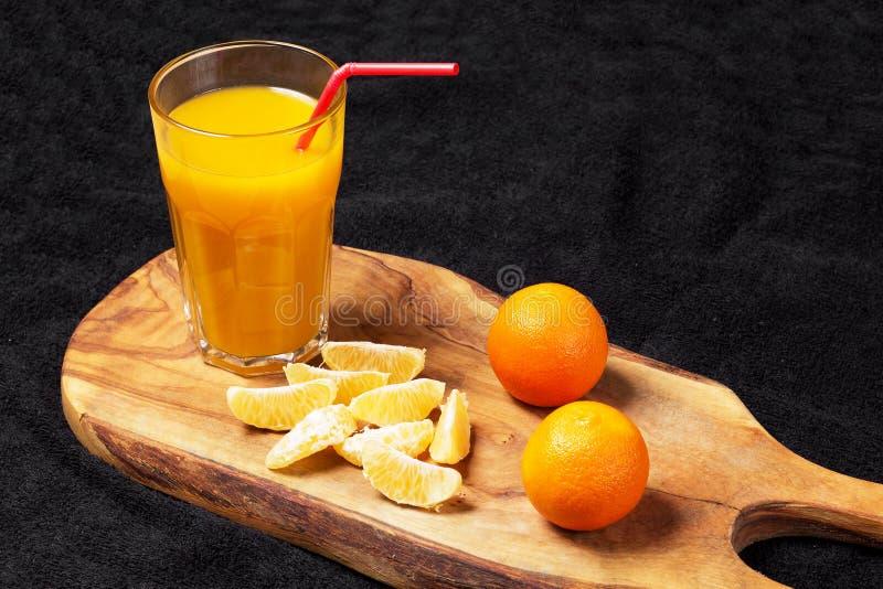 Diverso citrino maduro e um vidro do suco em uma tabela de madeira em um quadro-negro - os mandarino fotos de stock