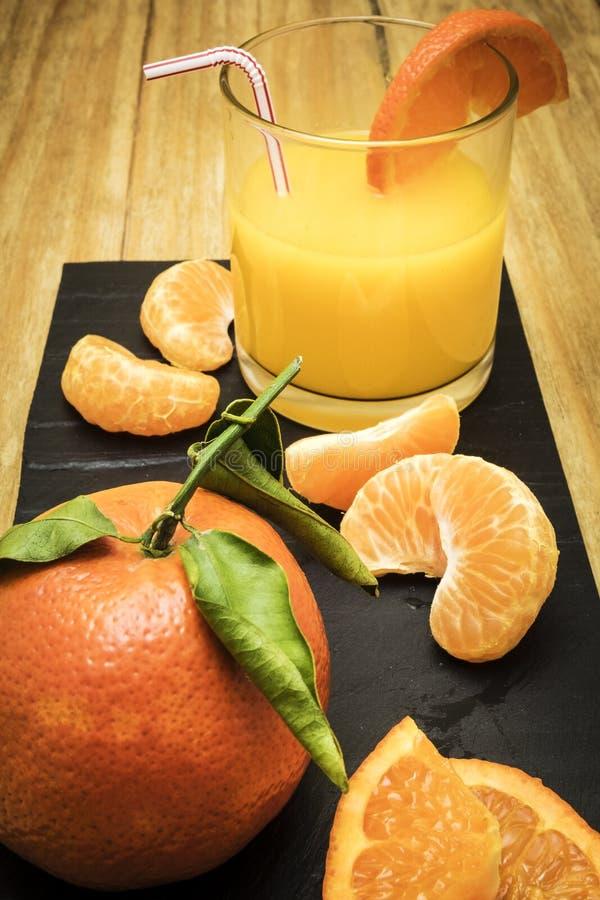Diverso citrino maduro e um vidro do suco em uma tabela de madeira em um quadro-negro foto de stock royalty free