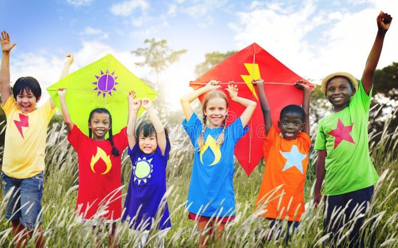 Diverso concetto di gioco dei giovani del campo dell'aquilone dei bambini fotografia stock