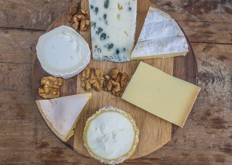 Diverso de quesos franceses en la tabla de cortar de madera imagenes de archivo