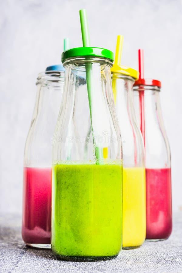Diverso del smoothie y de bebidas en botella con la paja en el fondo de madera ligero, vista lateral fotos de archivo libres de regalías