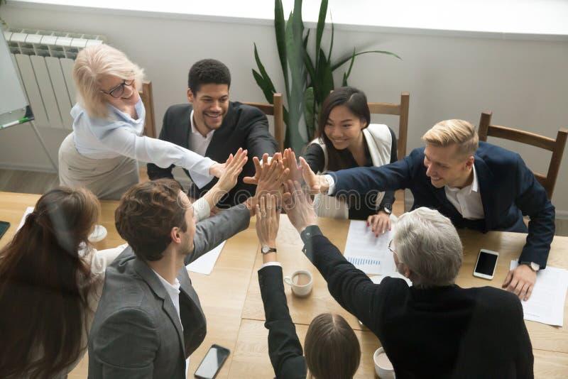 Diverso gruppo di affari che dà unità di mostra di livello cinque, vista superiore immagini stock