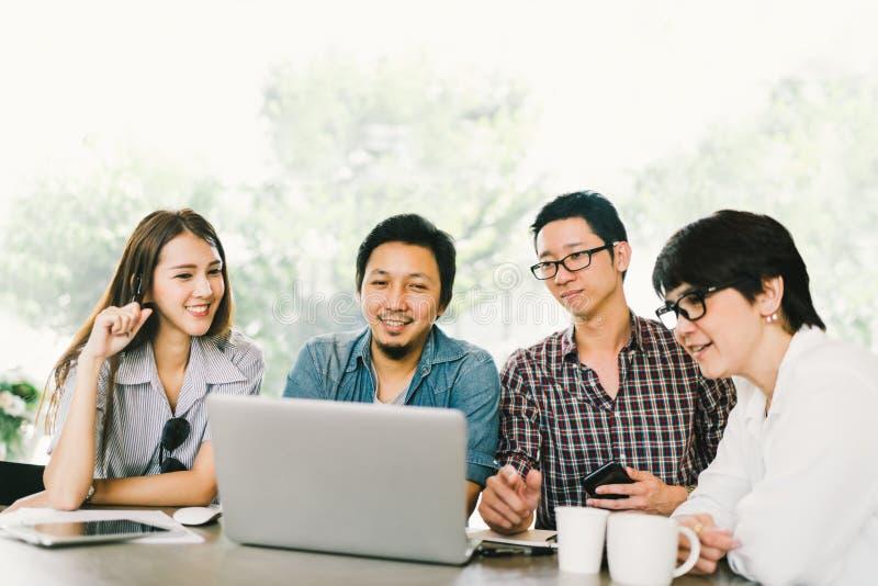 Diverso gruppo di colleghe o di studenti di college asiatici di affari che utilizzano computer portatile nella riunione casuale d fotografia stock libera da diritti