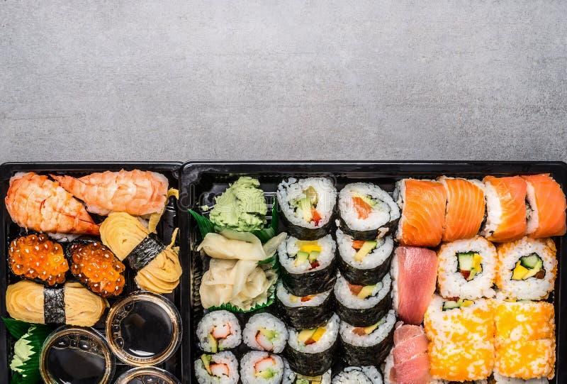 Diverso menú del sushi en caja negra del transporte o caja del bento en el fondo de piedra gris, visión superior fotografía de archivo