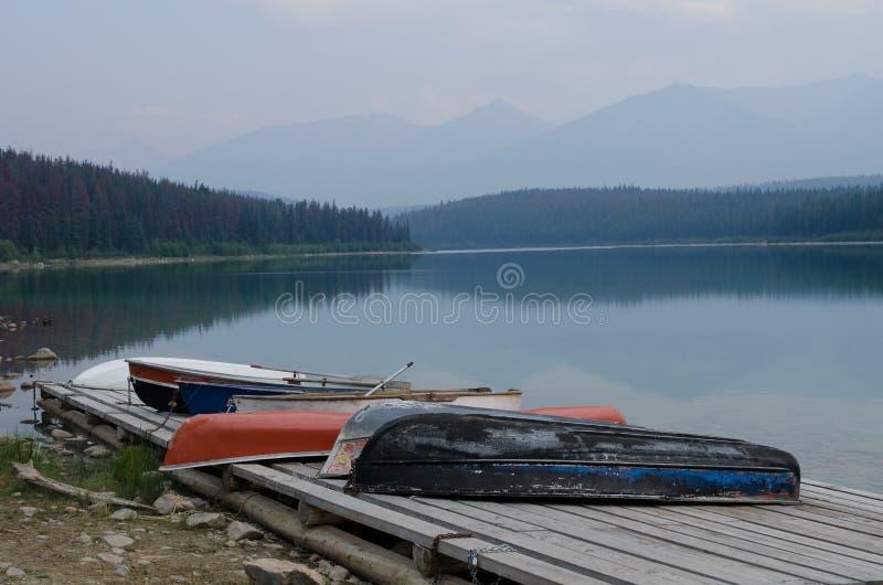 Diverso overturnedd de los barcos que reman en un muelle puesto a tierra con un lago cubierto niebla tranquila y montañas en el f imagen de archivo libre de regalías