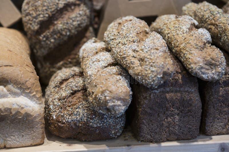 Diverso pan entero del grano en estante de madera en panadería imagen de archivo