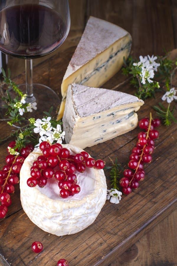 Diverso queso con el molde blanco y azul Un vidrio de vino rojo y de bayas frescas de la pasa roja Flores blancas Fondo de madera imagen de archivo libre de regalías