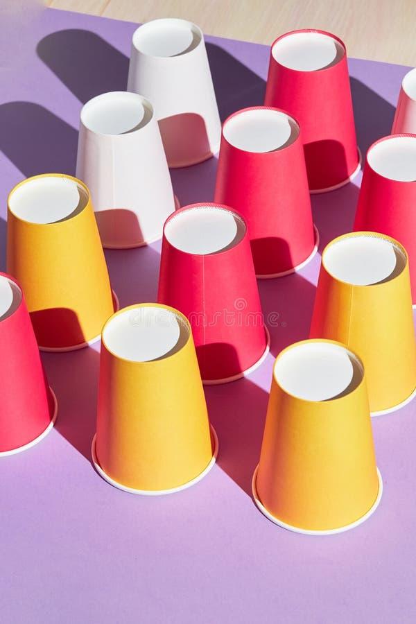 Diverso sistema plástico colorido de las tazas del partido, aislado en fondo azul fotografía de archivo libre de regalías