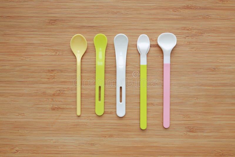 Diverso tipo de cucharas plásticas para los bebés en el fondo de madera del tablero fotos de archivo libres de regalías
