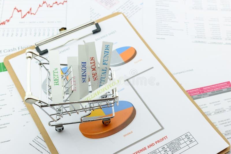 Diverso tipo de productos financieros y de la inversión en una carretilla imagen de archivo