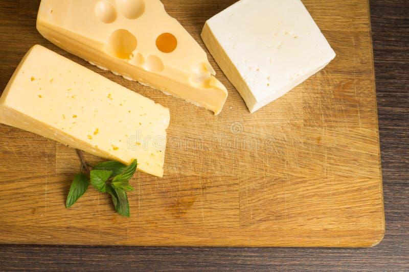 Diverso tipo de queso en el tablero de madera imagen de archivo