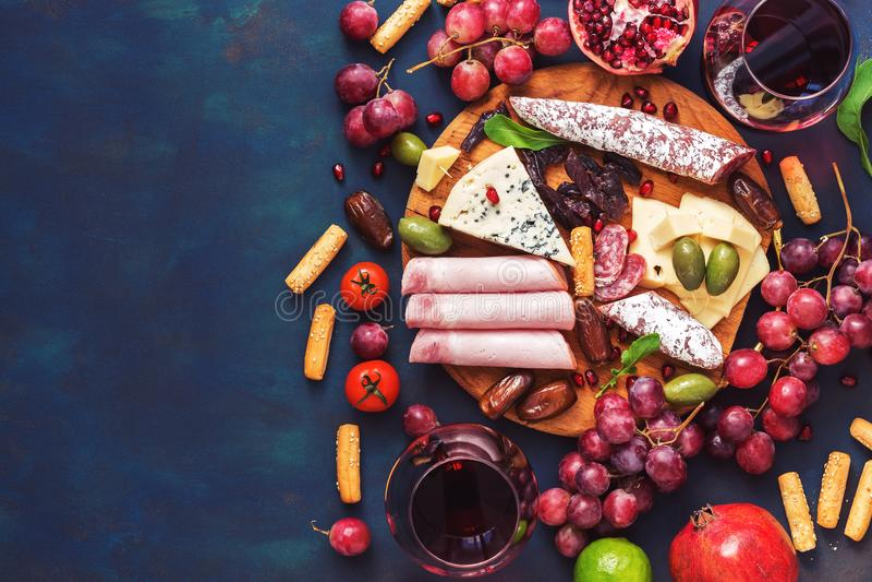 Diverso vino aperitivo-rojo, frutas, salchichas, queso, verduras en un fondo oscuro del finem Copie el espacio, visión superior imagenes de archivo