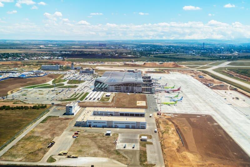Diversos aviones se colocan al lado del edificio del aeropuerto del Si foto de archivo