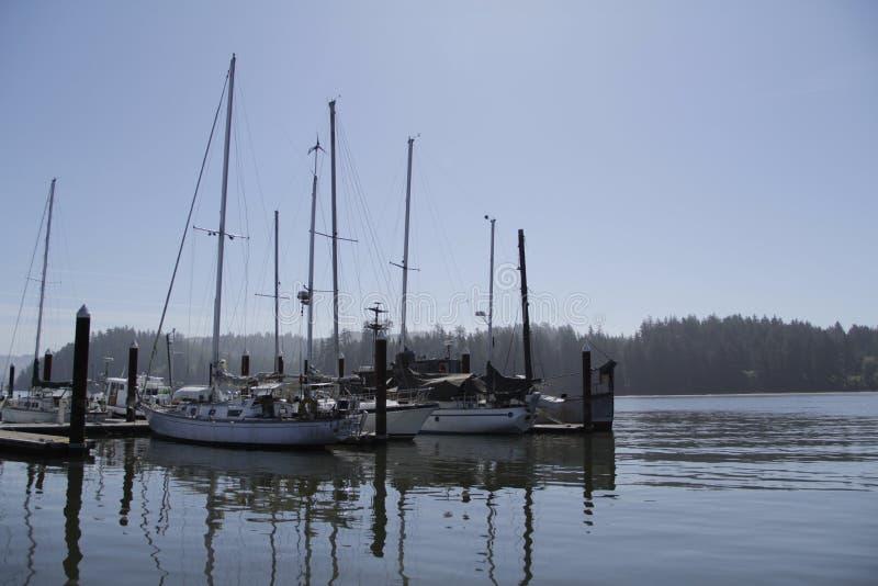 Diversos barcos entrados na baía com montanhas imagens de stock