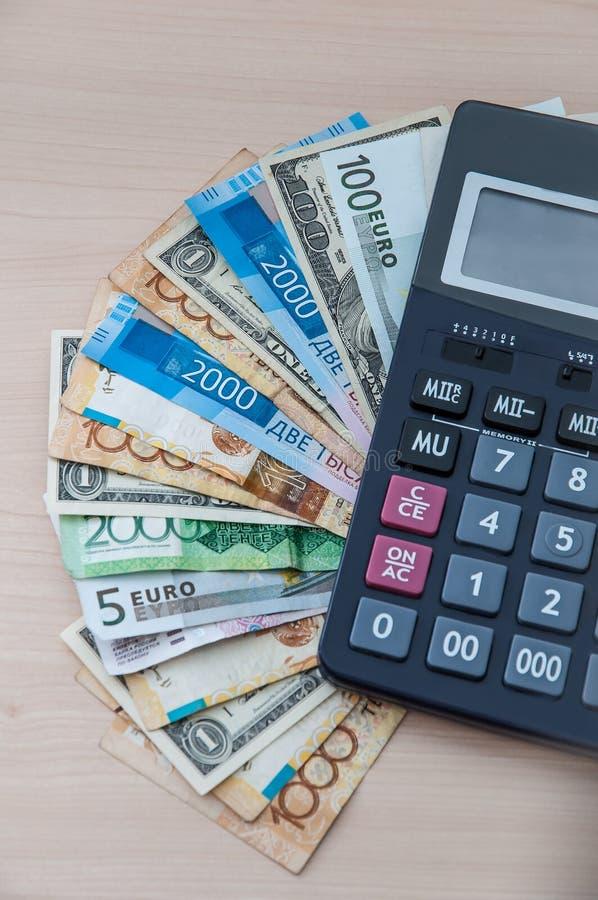Diversos billetes de banco de diversas denominaciones se apilan en una fan y una calculadora foto de archivo