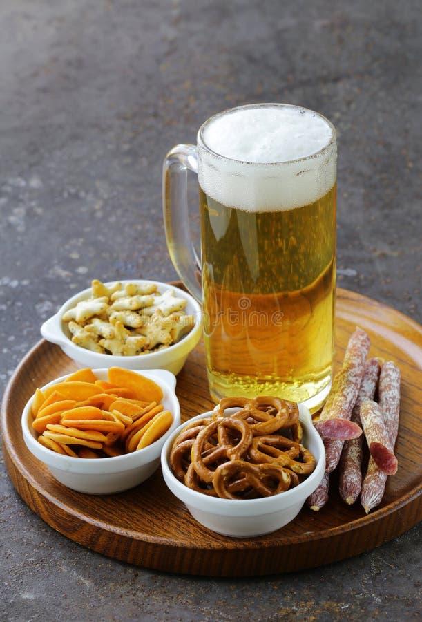 Diversos bocados salados y un vidrio de cerveza fresca fotos de archivo libres de regalías