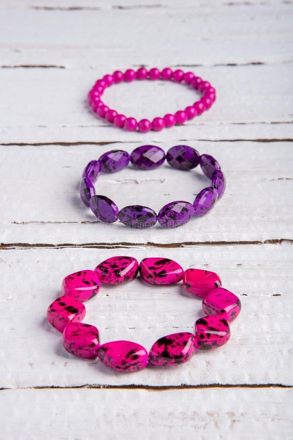 Diversos braceletes bonitos dos grânulos e pedras do rosa e do purp imagens de stock royalty free