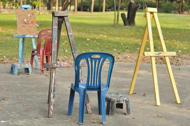Diversos caballetes de madera con las sillas plásticas en jardín público. imagen de archivo