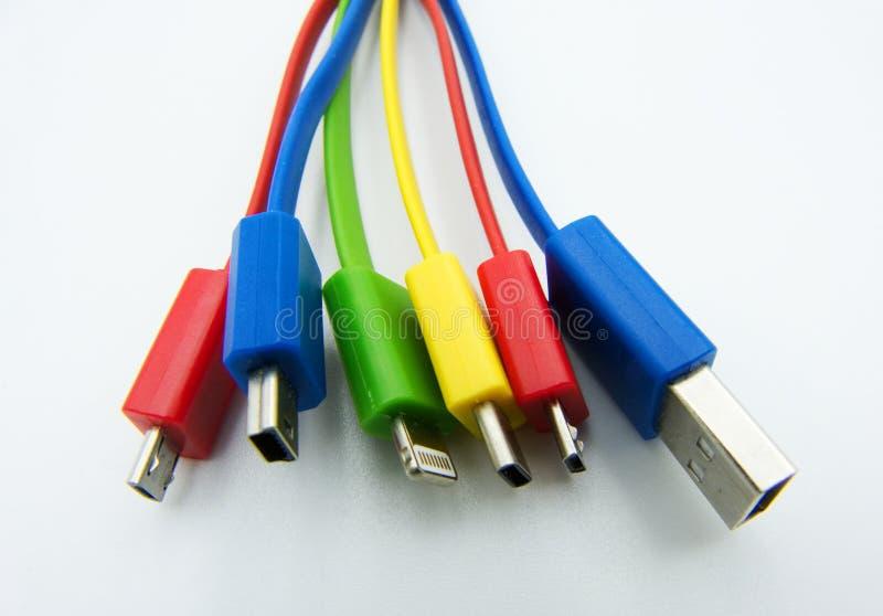 Diversos cables para el ordenador y los dispositivos electr?nicos en el fondo blanco imagen de archivo