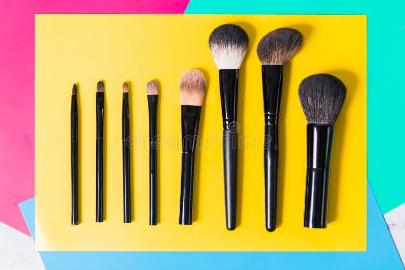 Diversos cepillos del maquillaje en un fondo amarillo brillante, primer, fotografía de archivo